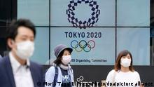 Pedestrians walk past an electric signboard showing the Tokyo Olympics Emblem, in Tokyo, June 3, 2021. The Japanese government told that the government remains committed to holding the games as scheduled. JIJI PRESS PHOTO/MORIO TAGA