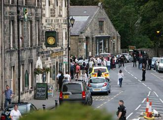 Members of the public gather at the police cordon, on a street in Rothbury