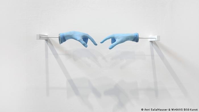 Installtion of blue gloves trying to meet one another.