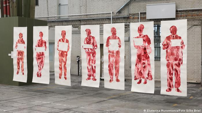 Ekaterina Muromtseva artwork 'Picket': paintings of 7 larger-than-life, blood red figures showing an empty sign.