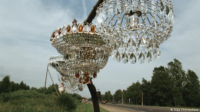Olga Chernysheva artwork 'On the Sidelines': A photo of three chandeliers hanging from a roadside tree.