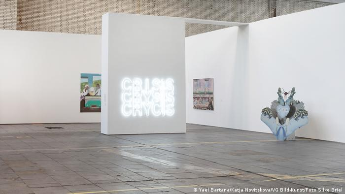 Open exhibition space with divider including a neon display saying crisis.