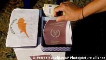 A demonstrator takes a mock copy of Cyprus passport during a demonstration against corruption outside of the conference center in the capital Nicosia, Cyprus, Wednesday, Oct. 14, 2020. Protesters called for the resignation of Cyprus' Parliamentary Speaker Demetris Syllouris amid corruption allegations involving the country's now defunct citizenship-for-investment program. (AP Photo/Petros Karadjias)