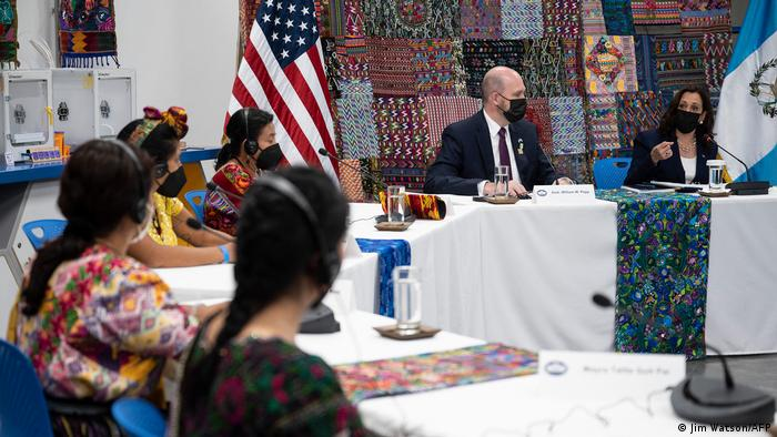 US Vice President Harris and US Ambassador William Popp at a table with traditionally dressed women