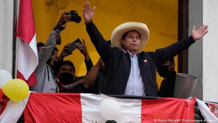 Perus gewählter Präsident Pedro Castillo breitet die Arme aus auf einem mit peruanischer Flagge geschmückten Balkon