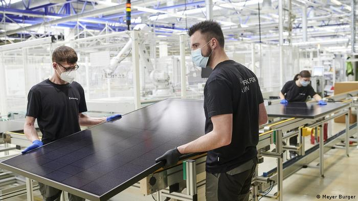 Two factory workers lift a solar panel