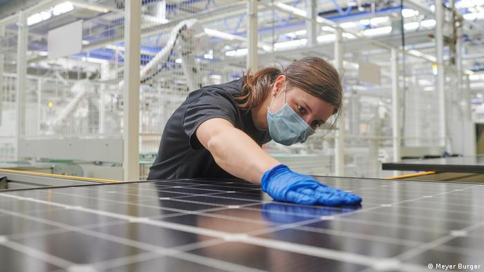 A woman conducts quality control on a solar panel