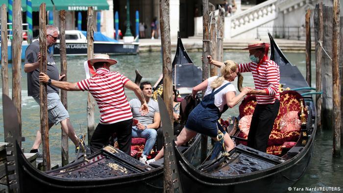 Fahräste besteigen eine klassische venezianische Gondel. Gondolieri mit Schutzmasken helfen