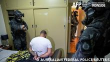"""A person is detained by Australian Federal Police after its Operation Ironside against organised crime in this undated handout photo released June 8, 2021. Australian Federal Police/Handout via REUTERS ATTENTION EDITORS - THIS IMAGE HAS BEEN SUPPLIED BY A THIRD PARTY. MANDATORY CREDIT. MUST CREDIT """"AUSTRALIAN FEDERAL POLICE"""". NO RESALES. NO ARCHIVES."""