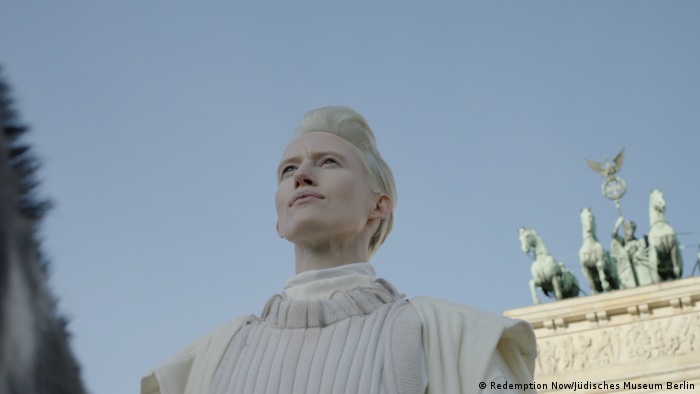A woman gazes into void , behind her a glimpse of part of the Brandenburg Gate