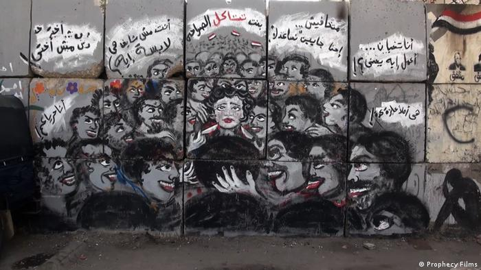 Film still 'As I Want': A graffiti of a bunch of men circling a woman in a threatening way.