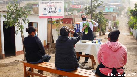 Ein Mann steht an einem draußen gedeckten Tisch und hält ein Gemüse hoch, eine Gruppe sitzender Frauen hört ihm zu