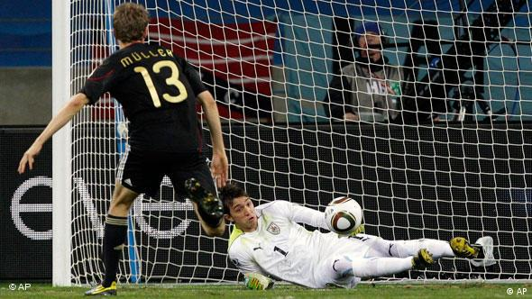 Germany's Thomas Mueller, center, scores his side's opening goal past Uruguay goalkeeper Fernando Muslera, right, during the World Cup third-place soccer match between Germany and Uruguay at Nelson Mandela Bay Stadium in Port Elizabeth, South Africa, Saturday, July 10, 2010.