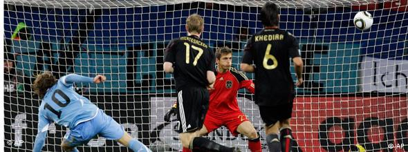 Uruguay's Diego Forlan, left, scores a goal past Germany goalkeeper Joerg Butt