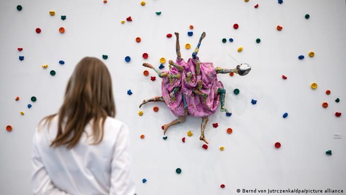 A spectator views a sculpture by Kris Lemsalu, with a dancer-like figure with spots surrounding it.