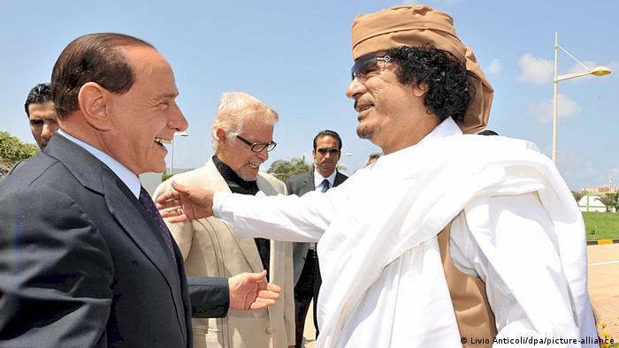 سنة 2008 العقيد الليبي معمر القذافي مستقبلا رئيس الحكومة الإيطالي سيلفيو برلسكوني