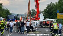 Einsatzkräfte der Feuerwehr haben mit Hilfe eines Krans das Wrack eines abgestürzten Kleinflugzeugs aus der Böschung einer Straße geborgen. Bei dem Absturz waren zwei Menschen ums Leben gekommen.