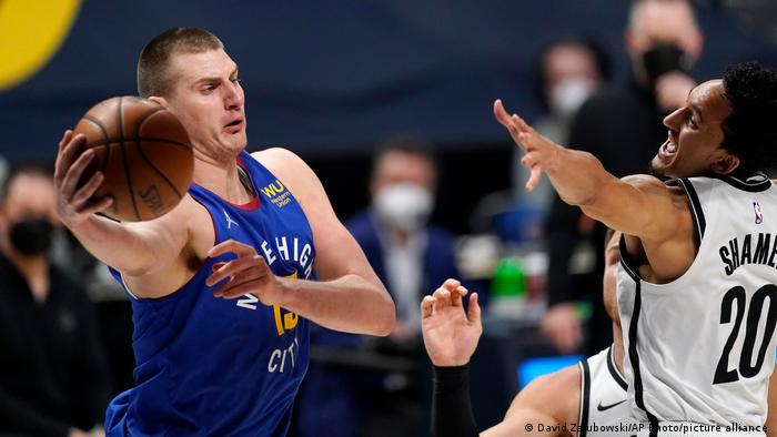 Denver Nuggets center Nikola Jokic, left, passes the ball as Brooklyn Nets guard Landry Shamet defends during the first half of an NBA basketball game Saturday, May 8, 2021, in Denver.
