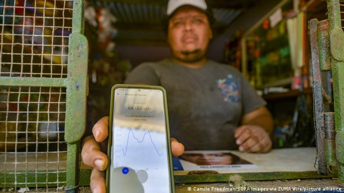 A shopowner in El Salvador holding a phone displaying Bitcoin price changes