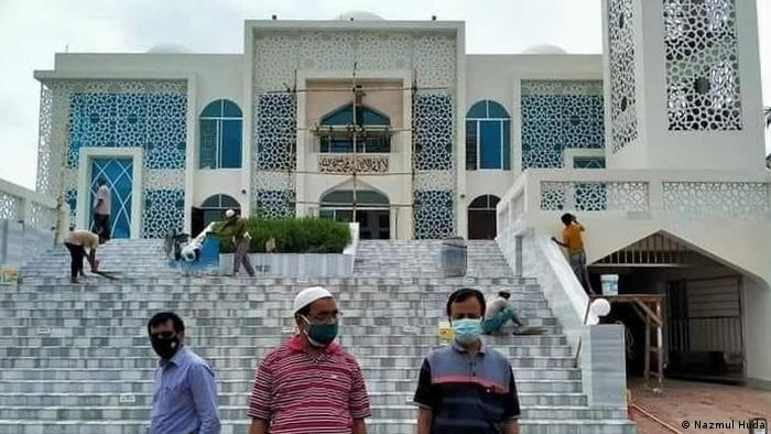 Men in front of a newly built model mosque in the Bangladeshi capital Dhaka