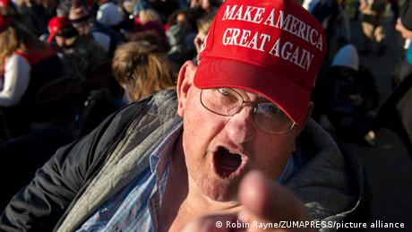 Man in MAGA hat yelling and pointing