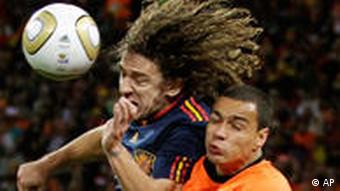 Spain's Carles Puyol, left, competes for the ball with Netherlands' Gregory van der Wiel