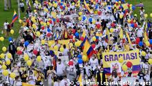 BOGOTA, COLOMBIA - MAY 30: Supporters of the government of President Ivan Duque wearing white t-shirts, holding white flowers, Colombian flags and signs in support of public forces take part in a movilization against violence on May 30, 2021 in Bogota, Colombia. According to José Uscátegui of Centro Democrático, public forces have suffered 2 casualties and around 1,000 police officers have been affected. 'Yo marcho por los héroes' is a mobilization called to raise the awareness of the damages caused by violence during the protests around the country which began on April 28. (Photo by Guillermo Legaria/Getty Images)