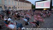 Visitors wait for the screening of the tv series 'Ich und die Anderen' (Me and the others) in front of the Charlottenburg palace as part of the 'Berlinale Summer Special' film festival in Berlin, Germany, Wednesday, June 9, 2021. (AP Photo/Michael Sohn, pool)