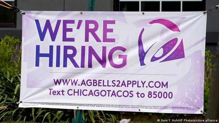 A hiring sign is displayed outside of a restaurant during the COVID-19 pandemic
