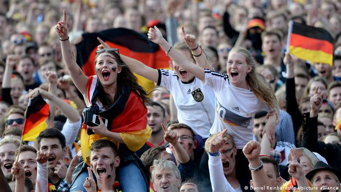 German soccer fans in 2014: two women sitting on mens' shoulders, with fans in the background waving flags.