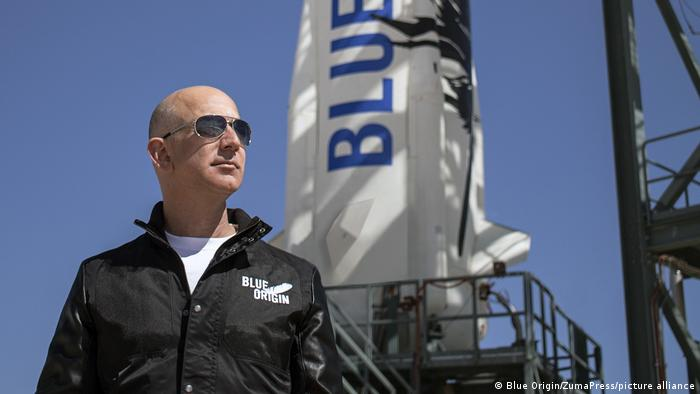 Jeff Bezoswears a jacket with a Blue Origin logo at a Texas launch site  - 57842956 401 - Virgin Galactic′s Richard Branson wins space race against Bezos | News | DW