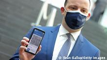 10/06/2021 BERLIN, GERMANY - JUNE 10: German Health Minister Jens Spahn holds up a smartphone with the CovPass Covid vaccination digital certificate on a smartphone through Germany's Corona Warn app on June 10, 2021 in Berlin, Germany. CovPass will provide those who have been fully vaccinated against Covid-19 international certification. Countries across the EU have been working on a common platform for digital vaccination certification in particular to promote international summer travel and tourism. (Photo by Sean Gallup/Getty Images)