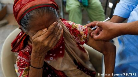 A woman covers her eyes as she receives a vaccine shot