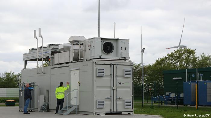 Deutschland Elektrolyseur in Haurup bei Flensburg. Mann steht neben einem grauen Container und dahinter ein Windrad.