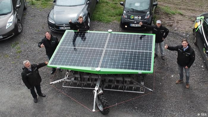 Mitarbeiter der Firma Firma Sonnenenergie Andresen in Sprakebül stehen neben einem etwa 8 Quadratmeter grossen Solarmodul auf einem Fahrgestell. (Farmdroid)