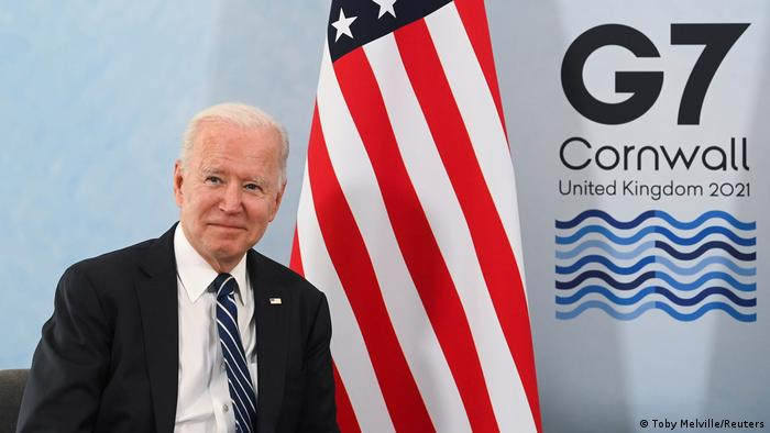 Biden in front of an American flag with a G7 logo