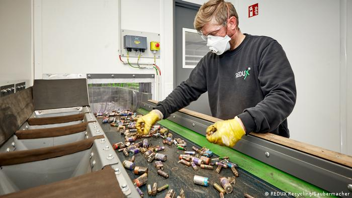 A worker at battery recycling specialist Redux sorting household batteries on a conveyor belt.