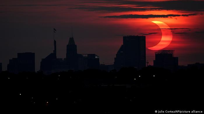 A partial solar eclipse rises over the Baltimore skyline, Thursday, June 10, 2021, seen from Arbutus, Md.