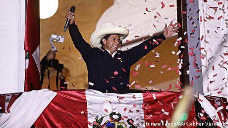 Pedro Castillo on a balcony in a straw hat amid confetti