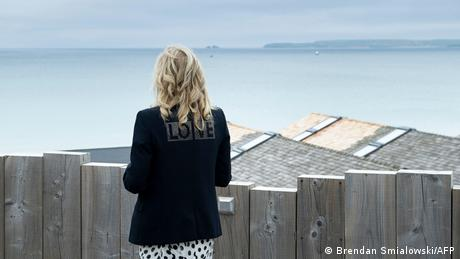 USA First Lady Jill Biden wearing a black jacket with the word 'love' on the back looks out to the see