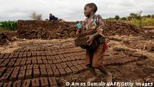 """*** Dieses Bild ist fertig zugeschnitten als Social Media Snack (für Facebook, Twitter, Instagram) im Tableau zu finden: Fach """"Images"""" *** A boy lifts dry raw bricks and takes them to a kiln where they will be burned during work to earn money at Jumpha Village, Traditional Authority Chitukula in Lilongwe, central Malawi, June 7, 2019. - Child labour is still a problem in Malawi due to two factors of poverty and culture. June 12 marks International Day against Child Labour. The International Labour Organization (ILO) launched the World Day Against Child Labour in 2002 to focus attention on the global extent of child labour and the action and efforts needed to eliminate it. Each year on June 12 , the World Day brings together governments, employers and workers organizations, civil society, as well as millions of people from around the world to highlight the plight of child labourers and what can be done to help them. (Photo by AMOS GUMULIRA / AFP) (Photo credit should read AMOS GUMULIRA/AFP via Getty Images)"""
