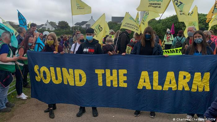 Protesters holding a sign reading 'Sound the Alarm'