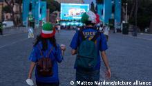 Two fans seen walking toward a large screen in Rome