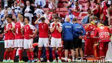 Denmark's players react as paramedics attend to Denmark's midfielder Christian Eriksen