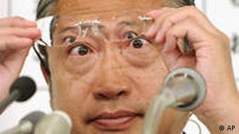 Yoshimi Watanabe checks his glasses as he watches the election results