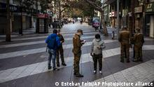 Police officers check the permissions of people walking in downtown Santiago, Chile, Saturday, June 12, 2021. The Chilean capitol has reinstated quarantine measures due to the increase in COVID-19 infections. (AP Photo/Esteban Felix)