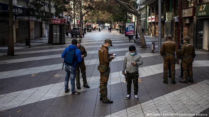 Police officers check people's papers in deserted downtown Santiago