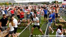 Auf einer Wiese stehen Tische und Bänke in getrennten Bereichen. Um die Tische herum sitzen und stehen jubelnde Fans, einige mit England-Fahnen.
