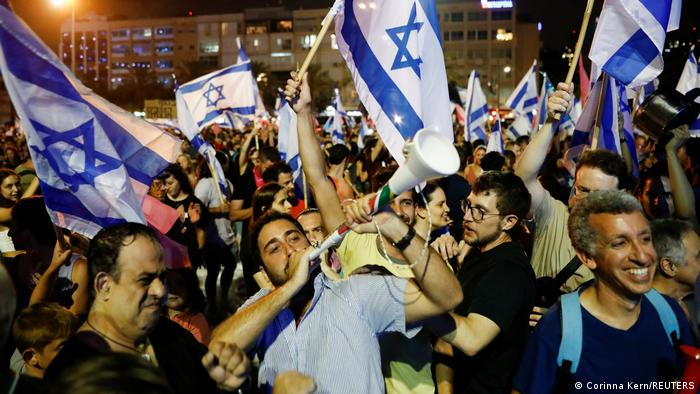 People celebrate after Israel's parliament voted in a new coalition government,