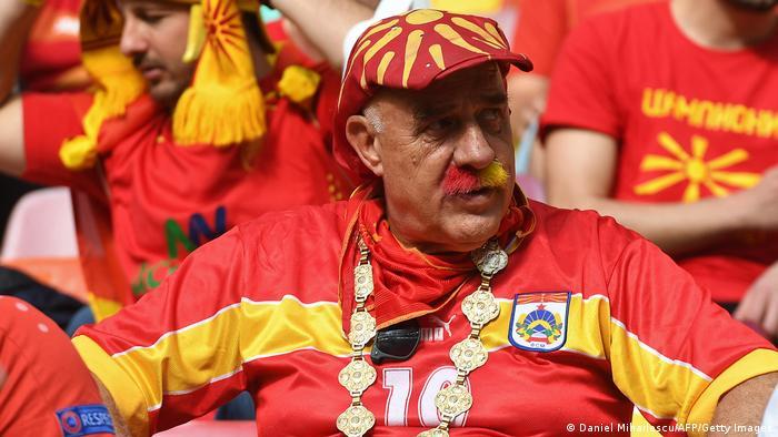 این هوادار تیم ملی فوتبال مقدونیه شمالی نه تنها لباسی به رنگ پرچم تیم ملی کشورش به تن کرده، بلکه سیبلهای خود را به رنگهای زرد و قرمز درآورده است. به قول معروف کار از محکمکاری عیب نمیکند.